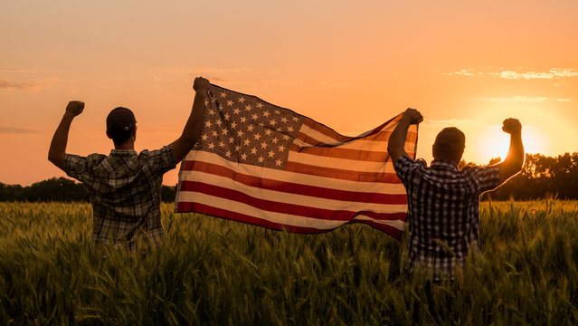 Two men happily raise the American flag over a field of wheat at sunset. 4th of july concept