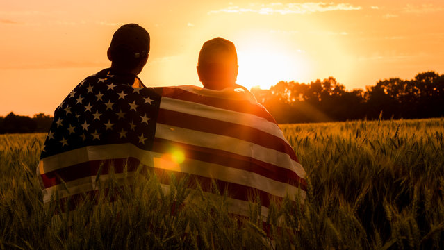 A man and his son admire the sunset over a field of wheat, wrapped in the flag of the USA