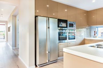 A modern refrigerator in the luxury kitchen with microwave ovens fixed to the wall