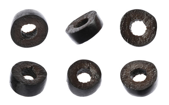 Set of flying cut black olives on white background, closeup