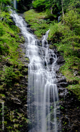 Wall mural vertical panorama of high picturesque waterfall in lush green forest landscape
