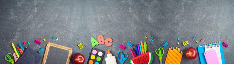 Back to school background with school supplies on blackboard.