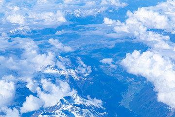 Aerial view of snowy high peaks of the Dolomites and small villages in northeastern part of Italy peeping through clouds.