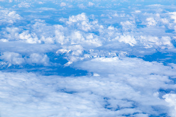 Aerial view of snowy high peaks of the Dolomites (mountain range, part of the Alps) in northeastern part of Italy peeping through clouds.