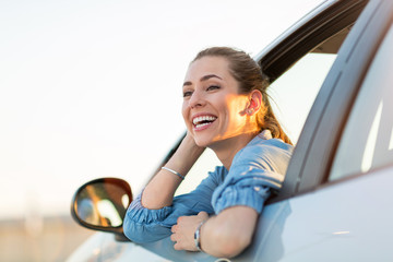 Happy woman driving a car and smiling Wall mural