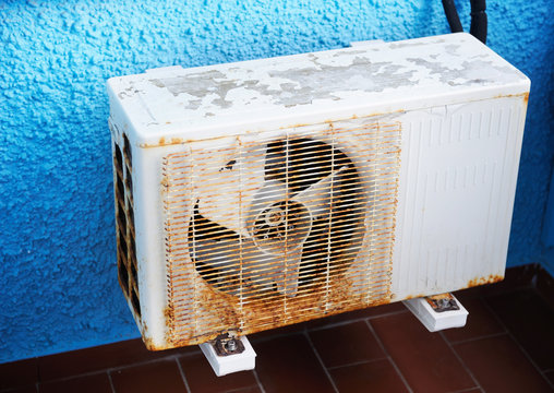 OLD  AIR CONDITIONER ON THE BLUE WALL
