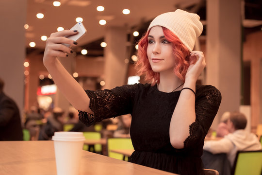 Beautiful girl with orange hair, in a cap photographes herself on a smartphone. Selfie on the phone. Sitting to wait friends alone at a food court in a cafe. Fashionable image. People Z.