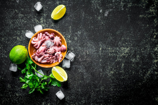 Baby octopus on a plate with slices of lime, ice and parsley.