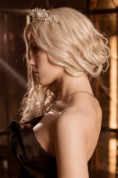 A beautiful, sexy young woman in a black evening dress, with a crown on her head and a necklace standing in profile. Close-up portrait.
