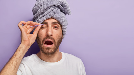 Photo of man plucks epilates eyebrows with pince, opens mouth, feels pain, has beauty treatments...