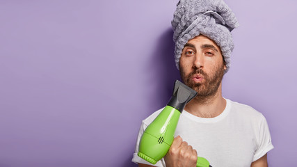 Funny handsome man holds hair dryer, blows lips, going to make haircut on festive event, has wrapped towel on head, stands indoor, free space for your slogan. Beauty and hair styling concept