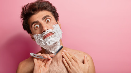 Surprised Caucasian man shaves with razor blade, has foam on face, stares at camera, shocked to have thick bristle, poses in home bathroom against pink background, blank space. Male gets ready for day