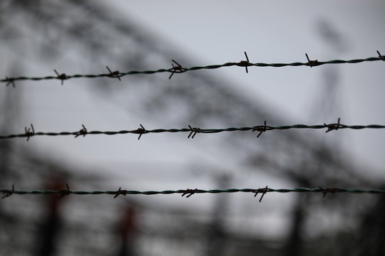 barbed wire with the blurred background of a refugee camp