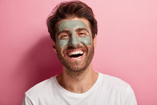 Joyful delighted man has clay mask on face, enjoys spa treatments, has broad smile, being in high spirit, cares about beauty, wears white t shirt, isolated on pink wall. Skin care and wellness concept