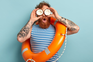 Embarrassed red haired young man with thick beard, keeps coconut on eyes, looks into distance, maintains water surveillance, carries lifering, poses over blue background. Life saving concept