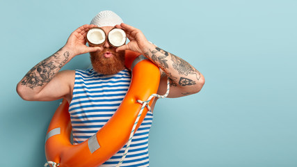 Horizontal shot of ginger male sailor looks into distance, uses coconut as binoculars, wears rubber swimhat, blue and white striped vest, has tattoo, models indoor over blue wall with free space