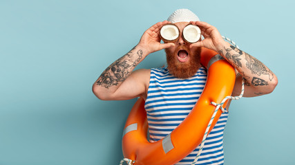 Surprised male lifeguard keeps two coconuts, has tattooed arms, wears striped sailor vest, carries orange lifering, cares about safety on water, isolated over blue wall. Boatswain with swim equipment