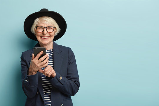 Cheerful female pensioner learns how to use smartphone, types notification, wears hat and jacket, connected to wireless internet. Charming granny stays in touch with gadget, isolated on blue wall