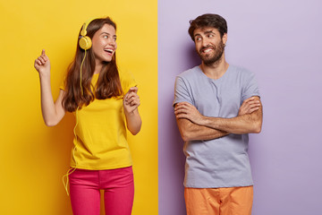 Positive lovely female dances and listens music in headphones, happy man with arms folded looks at girlfriend, being in good mood, pose over colorful background. People, music, leisure concept