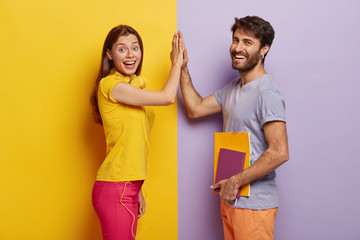 Positive young woman and man give high five, agree work as team, stand sideways, isolated over purple and yellow background. Male student with notepad touches palm of girlfriend, have agreement