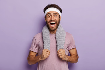 Happy male runner smiles broadly, surprised to cover long distance on marathon, has towel on neck, wears casual t shirt and white headband, isolated over purple background. Sport and training concept Wall mural