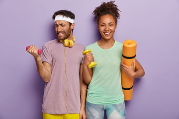 Sporty guy lifts heavy dumbbell, works on muscles, wears headband, casual purple t shirt, cheerful Afro girl with combed curly hair holds fitness mat. Multiethnic couple have active training together