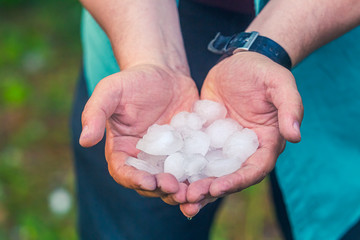 Man hand holding a hail after hailstorm