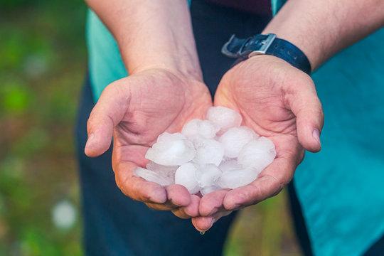 Man hand holding a hail after hailstorm