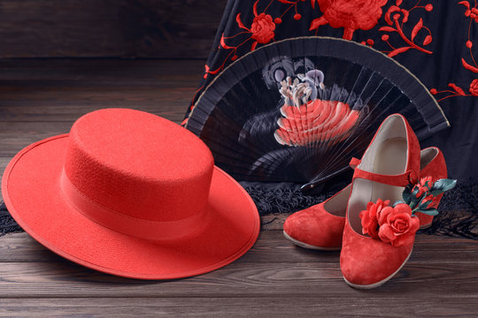 Beautiful and bright accessories for flamenco dance on a wooden background. Shawl, hat, fan, shoes, castanets and a flower for the hair.