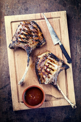 Barbecue dry aged tomahawk pork steak as top view on an old rustic board with knife