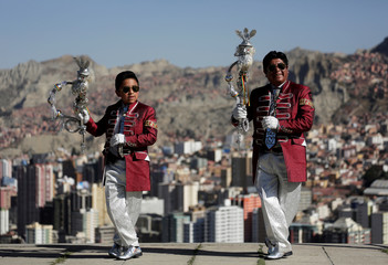 """Santos Poma and his grandson Ariel pose for a photo before a parade in honor of """"Senor del Gran Poder"""" (Lord of Great Power) in La Paz"""