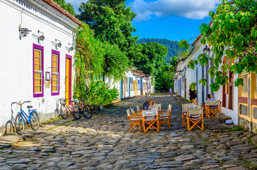 Wall Mural - Street of historical center  with tables of restaurant in Paraty, Rio de Janeiro, Brazil. Paraty is a preserved Portuguese colonial and Brazilian Imperial municipality