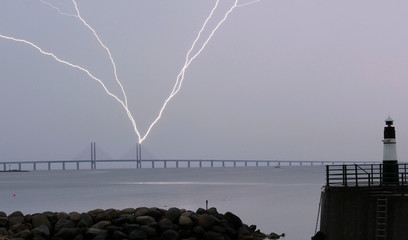 Lightning strikes the Oresund Bridge between Sweden and Denmark, during a thunderstorm, seen from Malmo