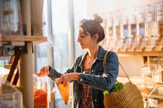 Beautiful young woman shopping in a bulk food store.