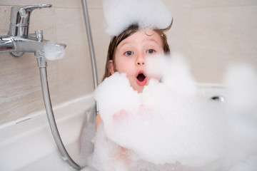 little girl in bath playing with foam