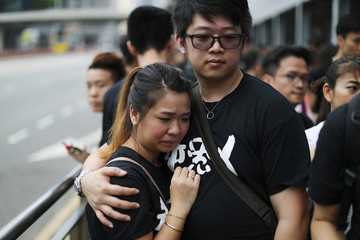 People react at the site where a man fell from a scaffolding at the Pacific Place complex while protesting against a proposed extradition bill, in Hong Kong