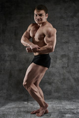 Sexy bodybuilder man posing in full growth on dark background in black shorts. Handsome pumped male body isolated with free space for advertising