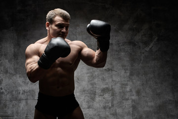 Muscular pumped man boxing in gloves on a black background. Sexy athletic body