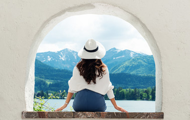 Wall Mural - Traveling in Europe, Young woman in white hat looking at beautiful mountain with lake view at Austria in summer