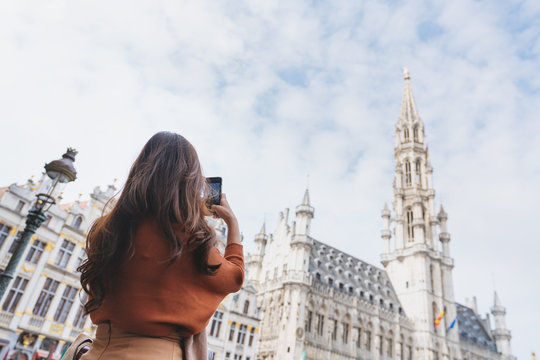 Travelling in Europe, Young woman taking photo by mobile smart phone at grand-palace in Brussels, Belgium in summer