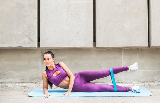 Young woman stretching the muscle strap. Fitness female trains rubber muscles of the hips.