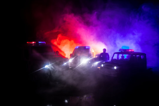 Police cars at night. Police car chasing a car at night with fog background. 911 Emergency response pSelective focus