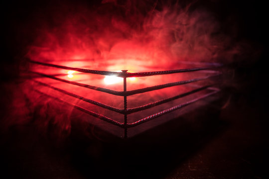Empty boxing ring with red ropes for match in the stadium arena. Creative artwork decoration
