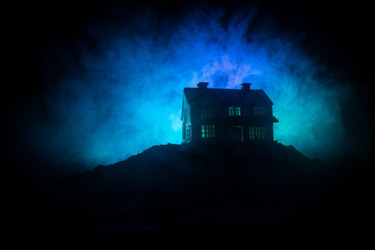 Old house with a Ghost in the forest at night or Abandoned Haunted Horror House in fog. Old mystic building in dead tree forest. Trees at night with moon. Surreal lights.