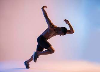 Muscular Shirtless African-American man sprinting in red and blue light Wall mural