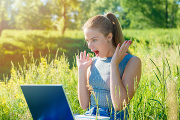 The girl is very surprised and happily looks at the laptop monitor. Sunlight in the corner of the frame.