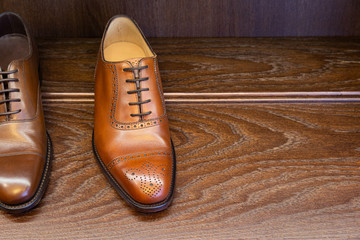 Brown full grain leather shoes on wooden display in men shoes boutique store.