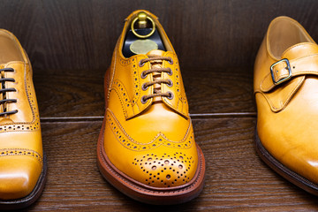 Tan full grain leather brogues shoes set on wooden display in in men shoes boutique store.