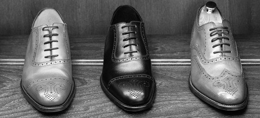 Full grain leather shoes on wooden display in men shoes boutique store. Black and white photo.
