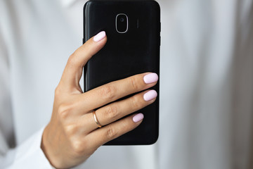 Close-up photo of elegant light pink manicure over white shirt background, tender women's hands with perfect nails hold a mobile phone